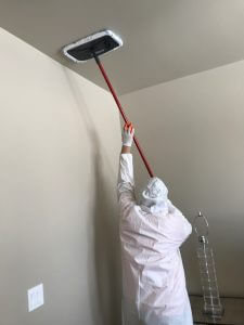 mold removal technician finishing a ceiling